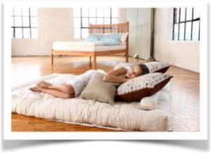 Девушка спит на матрасе на полу