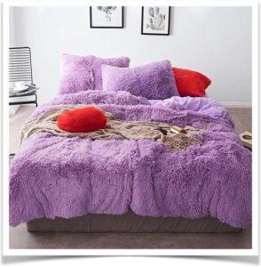 Кровать с сиреневым покрывалом и подушками