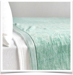 Зеленое покрывало из флиса на кровати