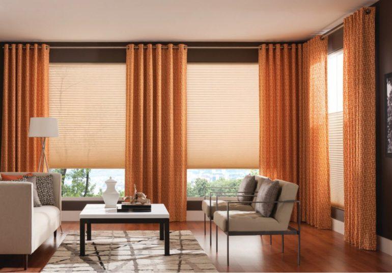 Оранжевые портьеры подходят в тон напольного покрытия и оригинально выделяются на фоне белой мебели