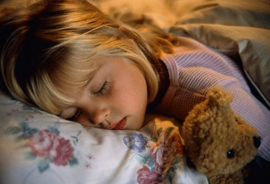 Девочка, спящая на подушке