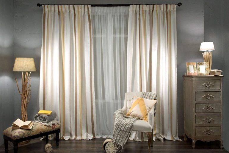 Холодные серые стены согреют теплые кремовые занавеси в золотистую полоску и декоративные элементы интерьера таких же тонов